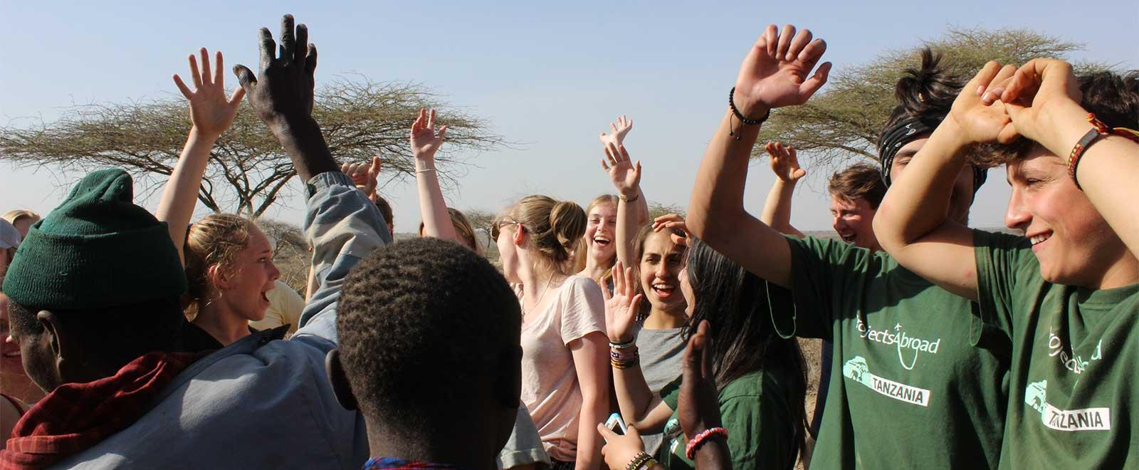 A group of volunteers abroad spend an afternoon learning about Masaai culture in Tanzania, Africa.